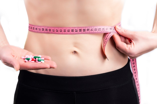 Slim woman holding weight loss pills and measuring tape on a light background, closeup
