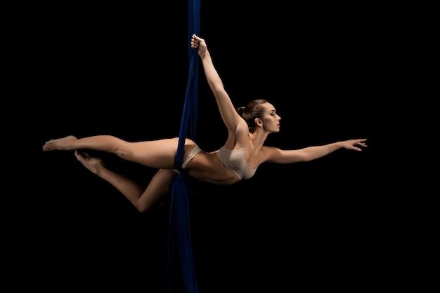 Стройная женщина в бежевом нижнем белье, упражнения на ткани, воздушная акробатика в воздушных тканях