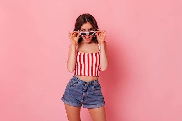 Стройная женщина в джинсовых шортах и полосатом топе надевает стильные солнцезащитные очки на розовой стене