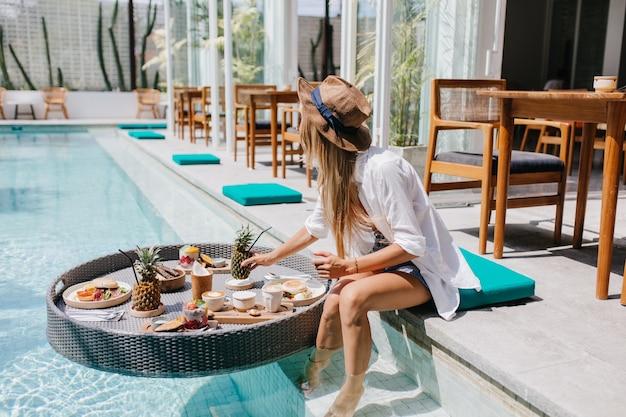 리조트 카페에서 달콤한 과일을 먹는 우아한 갈색 모자에 슬림 여자. 수영장에서 칵테일과 음식으로 편안한 흰 셔츠에 우아한 유럽 여자.