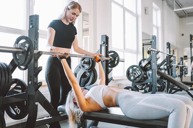 ベンチに横たわっているバーベルでパワートレーニングを行使するパーソナルトレーナーとジムのスリムな女性。