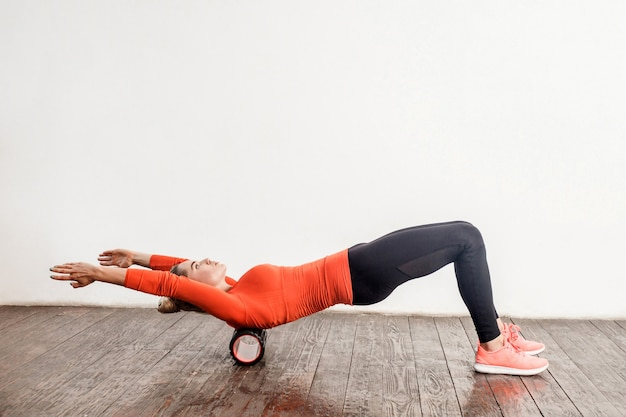 스포츠 타이트한 바지를 입은 날씬한 여성이 바닥에 폼 롤러 마사지로 운동을 하고 척추 근육을 이완하고 스트레칭하며 등을 훈련합니다. 집에서 건강 관리 및 운동. 실내 스튜디오 촬영