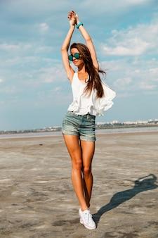 Тонкая женщина в белой футболке позирует возле пляжа.