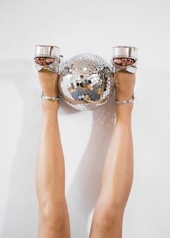 Slim woman legs holding disco ball