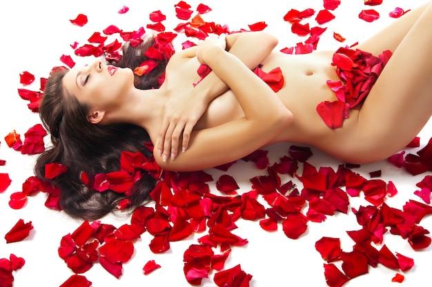 흰색 위에 빨간 장미 꽃잎에 누워 슬림 여자