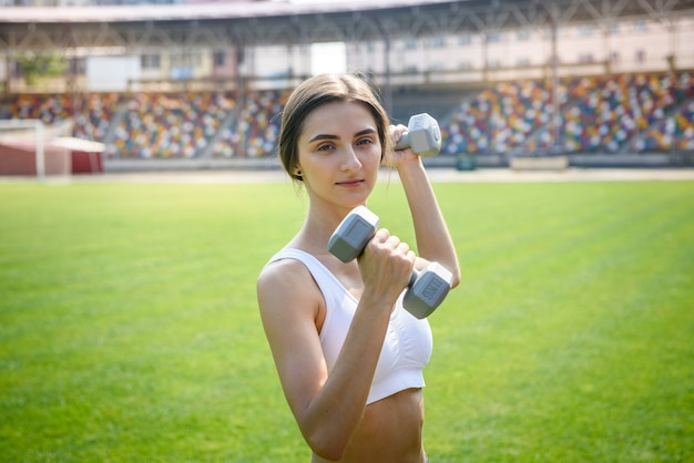 Slim woman making morning exercises with dumbbells on open air