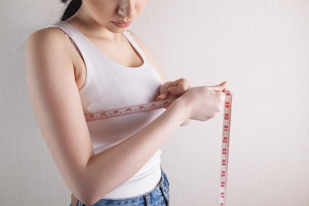 Стройная женщина измеряет грудь рулеткой