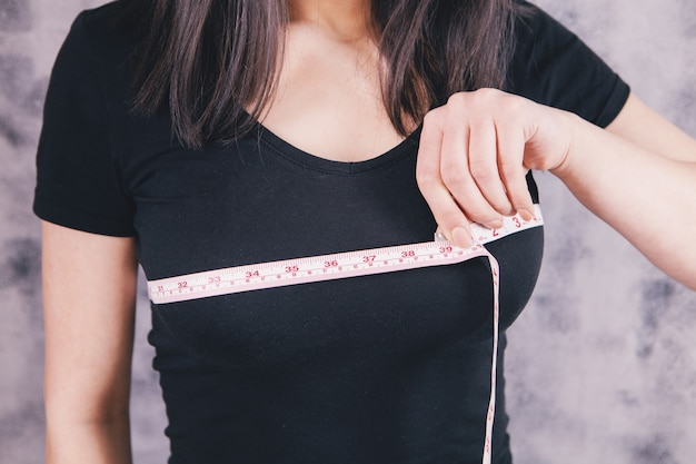 スリムな女性が巻尺で胸を測る