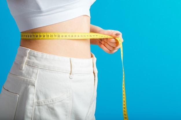 Худенькая женщина измеряет талию с помощью рулетки. концепция потери веса формирования здорового тела. тонкая талия, маленький живот в больших белых джинсовых брюках, изолированных на стене синего цвета. скопируйте пространство.