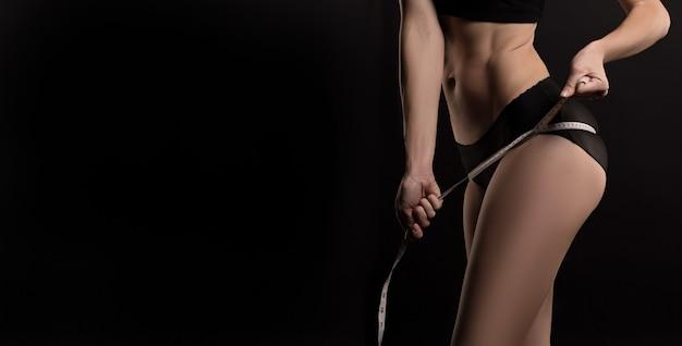 어두운 배경 위에 다이어트 후 측정 테이프로 그녀의 허벅지를 측정하는 슬림 여자