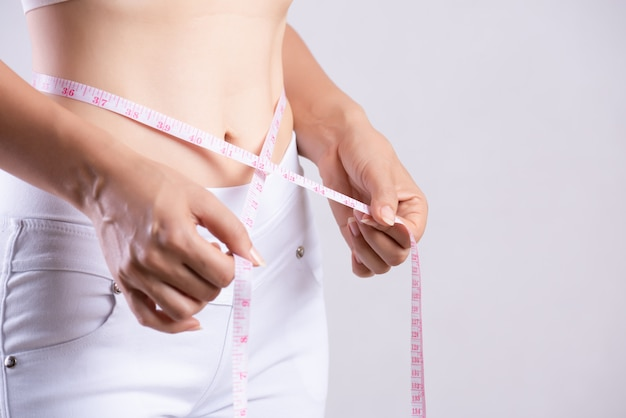 Slim woman measuring her thin waist with a tape measure. healthcare concept