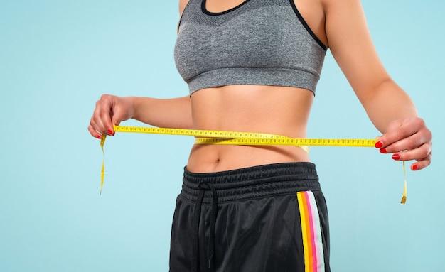 巻尺でウエストのサイズを測定するスリムな女性。青い背景で隔離。