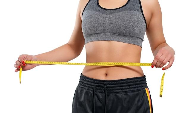 巻尺でウエストのサイズを測定するスリムな女性。白い背景で隔離。