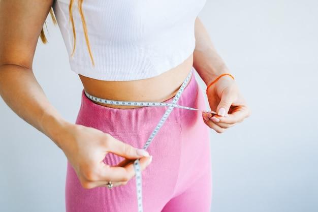 흰색 바탕에 줄자로 허리 사이즈를 측정하는 날씬한 여성. 성공적인 체중 감량. 슬림핏 컨셉입니다.