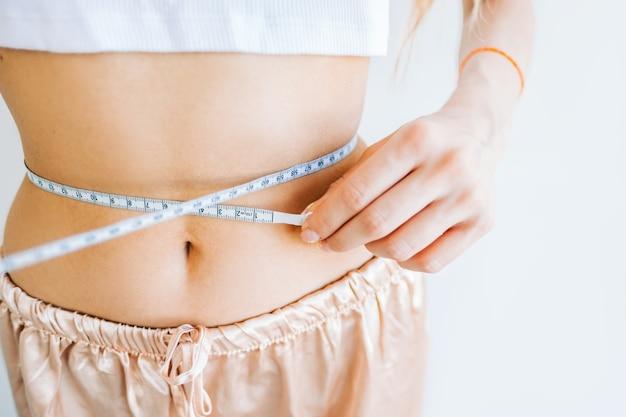 흰색 바탕에 줄자로 허리 사이즈를 측정하는 날씬한 여성. 성공적인 체중 감량.