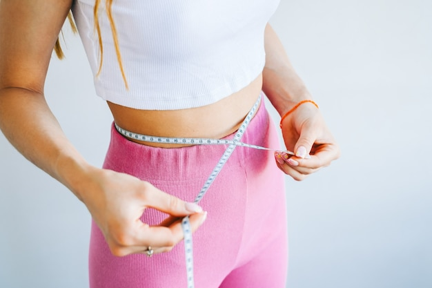 Slim woman measuring her waist's size with tape measure on white background. successful weight loss. slim fit concept.