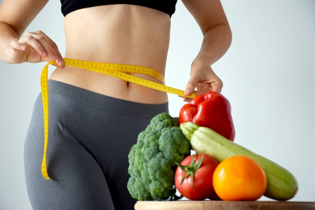 Slim woman measuring her waist size with tape measure and set of fresh vegetables on cutting board in defocus.