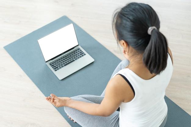 スリムな女性は、リラックスした座位で呼吸を定義しながら瞑想します。健康な女性は、インターネット ビデオでコーチとオンラインでトレーニングします。現代的なヨガのクラスは、自宅やジムで受講できます。
