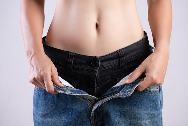 Slim woman in oversized blue jeans. healthcare and woman diet lifestyle concept