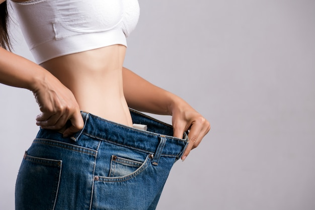 Slim woman in oversized blue jeans