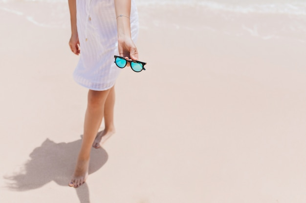 Slim woman posing at coastline with sunglasses. outdoor shot of relaxed barefooted woman  in white dress standing near ocean.