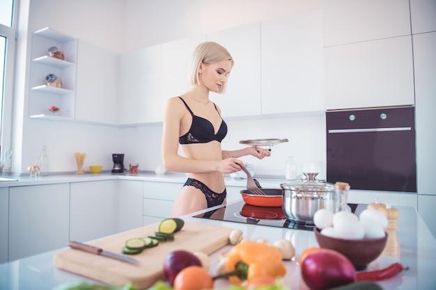 Стройная женщина позирует в нижнем белье на кухне