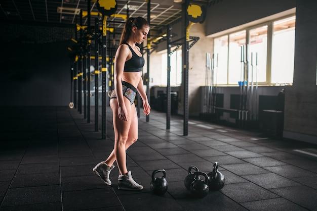 フィットネスクラブで体重をかけてポーズをとるスリムな女性。ジムでの魅力的な女性アスリートトレーニング