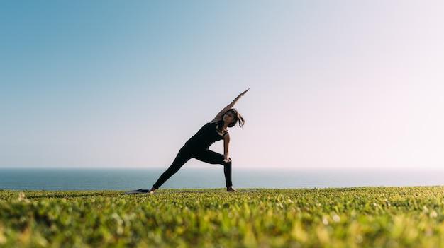 スリムな女性は自然な場所でヨガを練習します。コピースペース