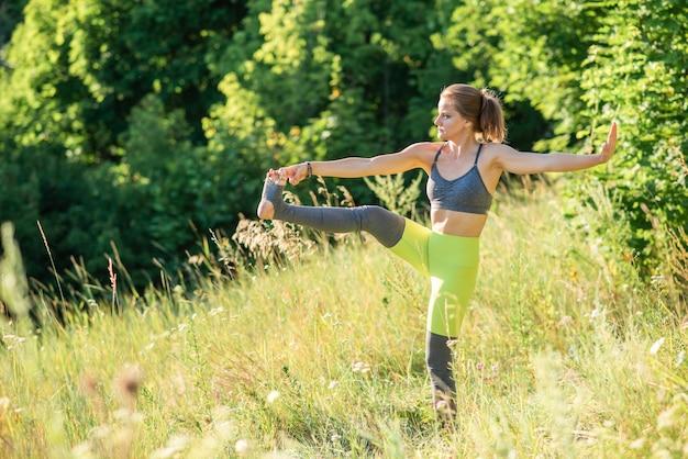 スリムな女性は晴れた日に自然の中でヨガを練習します