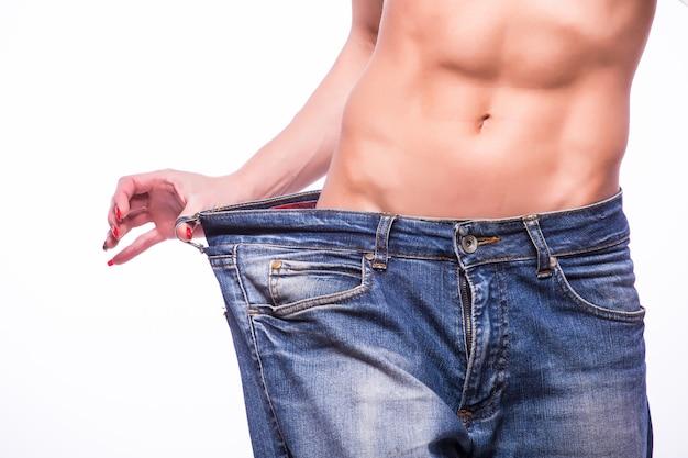 特大のジーンズを引っ張るスリムな女性。減量の概念。白い壁に隔離