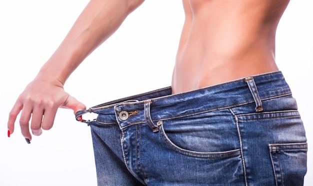 Donna esile che tira i jeans oversize. concetto di perdita di peso. isolato sulla parete bianca