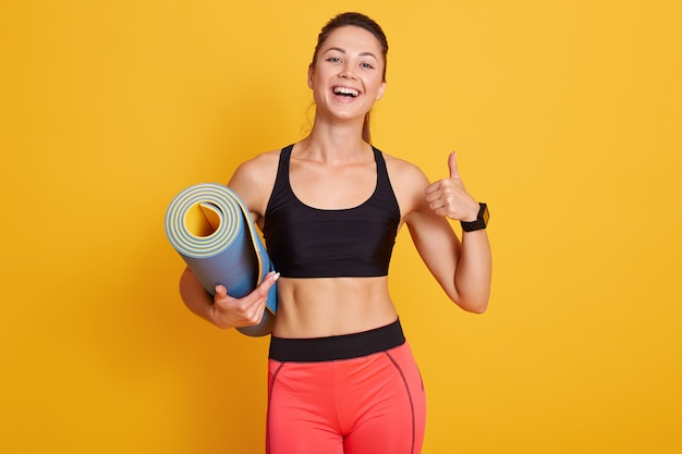 Slim woman ready for workout with yoga mat and thumbs up