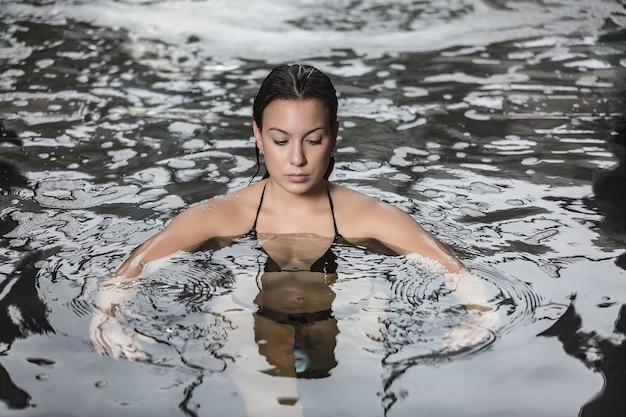 スパセンターで水でリラックスするスリムな女性