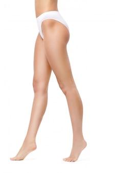 흰 벽에 고립 된 슬림 여자의 다리