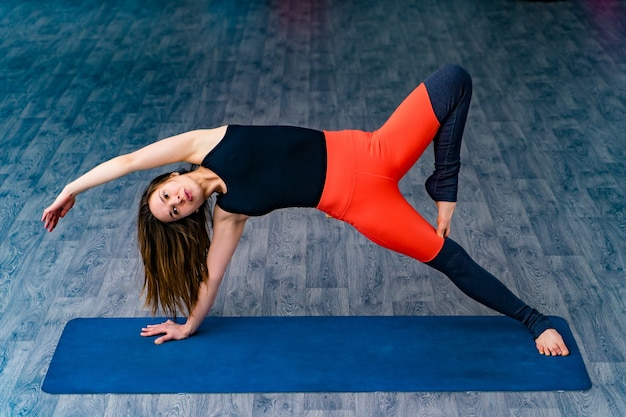 Slim woman in side plank pose at yoga class, vasisthasana exercise. female balancing on mat indoors at fitness gym