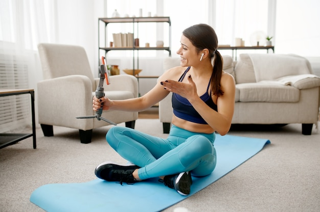 Стройная женщина сидит на коврике, онлайн-тренировка с телефоном