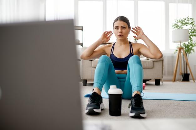 Стройная женщина сидит на коврике, онлайн-фитнес-тренинг на ноутбуке. женский человек в спортивной одежде, спортивная тренировка в интернете, интерьер комнаты