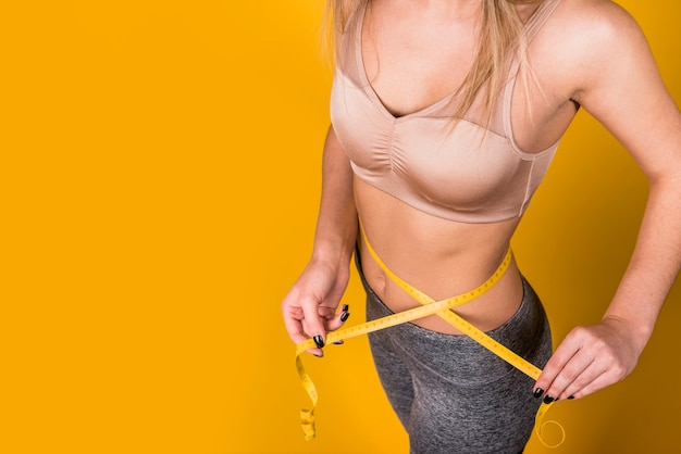 Slim woman in sportswear measuring waist by tape