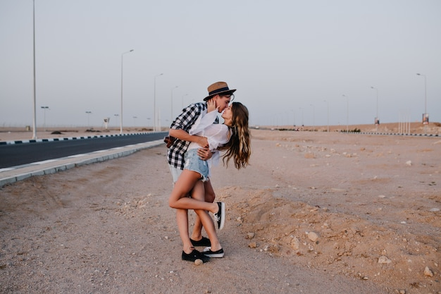 Slim woman standing in denim shorts on one leg, gently kisses her boyfriend on beautiful desert. stylish young man embracing his girlfriend, posing near the highway in summer vacation