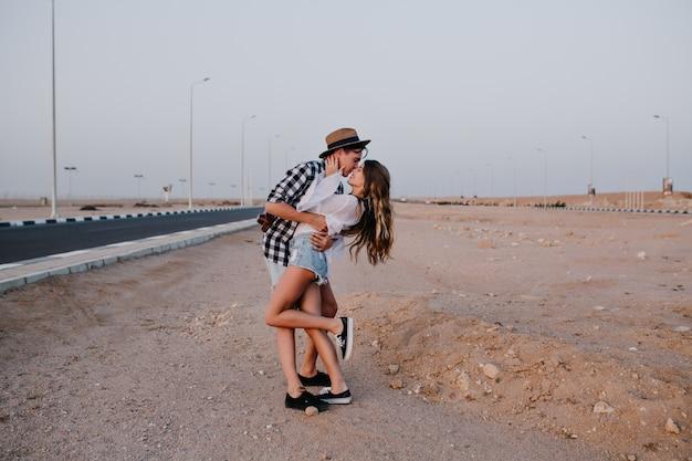 한쪽 다리에 데님 반바지를 입은 슬림 한 여성이 아름다운 사막에서 남자 친구에게 부드럽게 키스합니다. 여름 휴가에 고속도로 근처에서 포즈를 취하는 그의 여자 친구를 껴안은 세련된 젊은 남자
