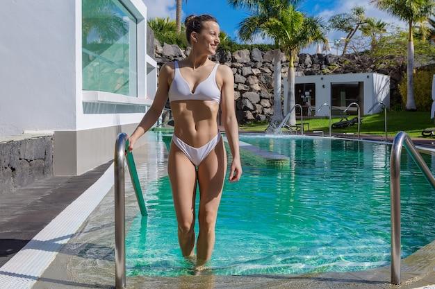 Стройная женщина, стоящая в бассейне