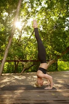 スリムな女性が頭の上に立って、バランス運動、サマーパークでのヨガトレーニング