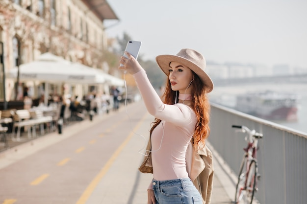 Slim woman in trendy beige hat making selfie with serious face expression