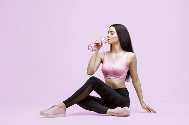 Slim woman in trendy sportswear drinking water from bottle to stay hydrated after workout
