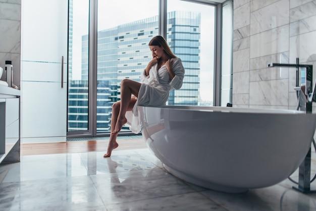 Slim woman wearing bathrobe sitting on edge of bathtub filling up with water.