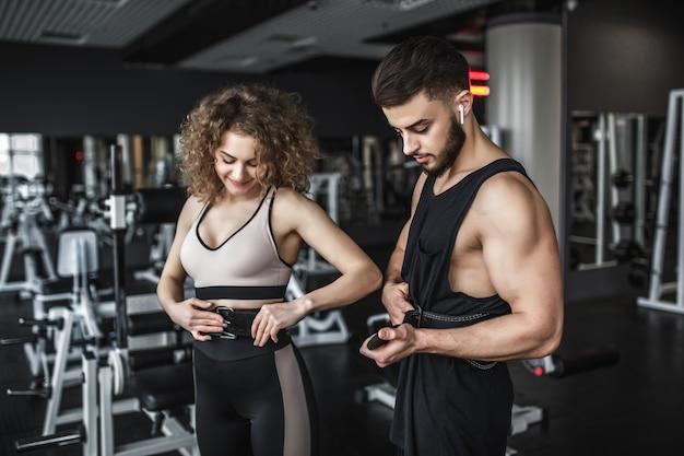 운동복을 입은 날씬한 여성은 벨트로 착용하고 체육관에서 훈련하는 동안 개인 트레이너