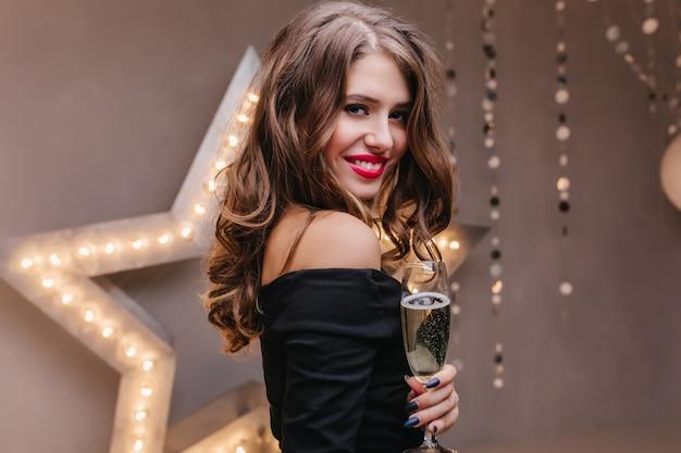 La donna esile indossa un abito nero in posa con il bicchiere di vino davanti alla stella splendente. ragazza europea dai capelli scuri che ride celebra qualcosa con champagne.