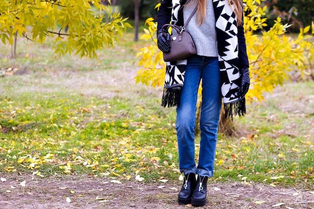 スリムな女性は、ブルージーンズと秋の森に立っている黒い靴を履いています。 10月の公園で小さな革のバッグでポーズをとって長いスカーフでトレンディな女の子の屋外のポートレート。