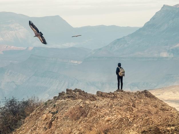バックパックを背負ったスリムな女性が崖の上に背を向けて立って、ワシが朝の空を飛んでいます。山の孤独、一人旅のコンセプト。