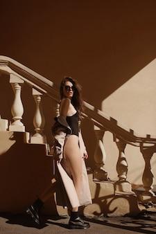 夏の晴れた日に屋外でポーズをとる黒いボディスーツとベージュのレインコートを着た完璧なボディのスリムな女性